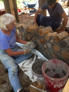 Jaki Roy of Earthwood Building School teaches students cordwood masonry construction at the Crazy Rooster Farm Cordood Class in June.